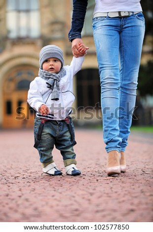 Toddler holding mother's hand outdoors