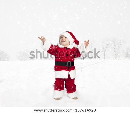toddler in santa claus outfit standing in the snow and looking up