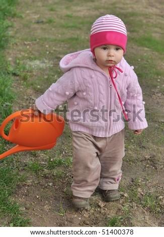 Toddler in the garden watering