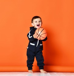 Toddler infant baby kid child hold basketball ball happy smiling laughing ready for game play in dark blue hoodie costume on orange background