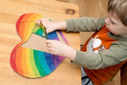 toddler inserting piece of heart shape rainbow puzzle. table game. brain exercises  at home. funny duck face, concentrated look. Montessori, fine motoric skills.
