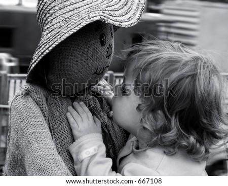 Toddler investigating scarecrow