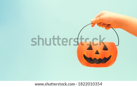 Toddler kid hands holding jack-o-lantern bucket ready for halloween. Children with candy bucket on blue background.Child having fun at Halloween trick or treat.Kids trick or treating.Autumn October