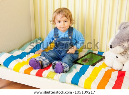 Toddler kid sitting with in the baby bed