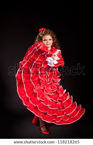 toddler little girl dancing flamenco in traditional spanish red dress. Adorable child from Andalusia with curly hair dancing Gypsy dance. Portrait of artist baby in carnival bellydancing costume.