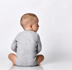 Toddler one-year-old baby boy in diaper and grey one-piece bodysuit with long sleeves sits back to camera looking aside with interest reading. Happy infancy and babyhood concept