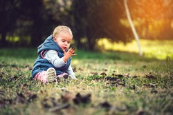 Toddler playing in grass and mud. Dirty hands, nature and immunity concept.