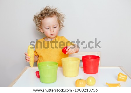Toddler playing with learning toys at home or kindergarten. Baby sorting organising objects blocks with specific colors. Early age education. Kids hand brain development activity for preschoolers.   Foto stock ©
