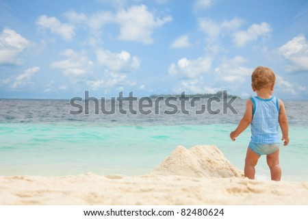 Toddler playing with sand on the tropical white beach