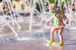 Toddler playing with small fountains on the urban plaza.