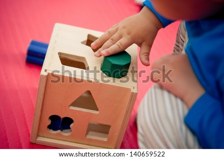 Toddler playing with wooden shape sorter