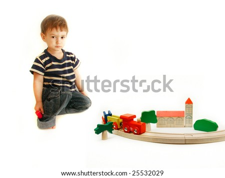 toddler playing with wooden train over white