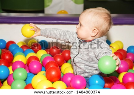 Toddler plays with colorful balls in playground. Ball pit poll at kids play center. #1484880374