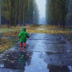 Toddler running in autumn rainy park