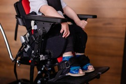Toddler sits in a special wheelchair at home. Child with cerebral palsy. Disability. Orthopedic shoes. Rehabilitation inclusion. Lifestyle