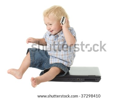 toddler sits on laptop while talking on cellular phone