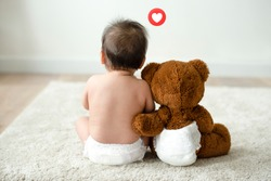 Toddler sitting beside his teddy bear