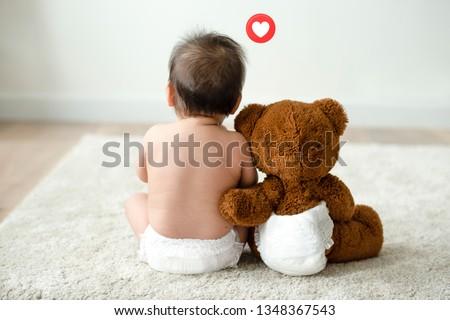 Toddler sitting beside his teddy bear