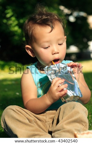 toddler sitting down on grass in park having a drink from a juice pack