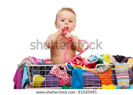 Toddler sitting in basket with clothes and holding hanger