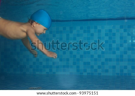Toddler swimming in the pool with copyspace left in the right sice