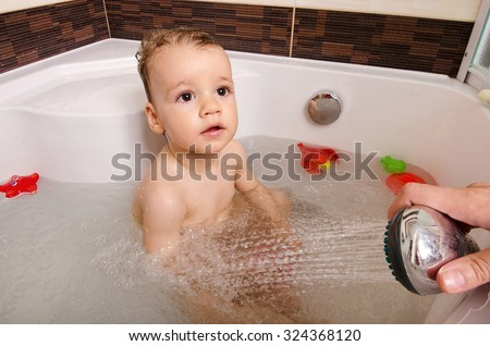 Toddler taking a bath. Little baby in a bathtub, mother\'s hand washing his hair with shampoo and soap. Kid playing with foam and water splashes. Clean kid after shower. Child hygiene