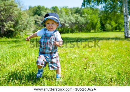 Toddler taking first steps in a park