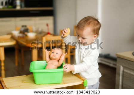 Toddler toddler bathes a toddler doll in a basin of water and a sponge, montessori and earlier child development