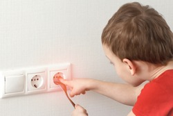 Toddler touches a power outlet. Dangerous children games at home with electricity.