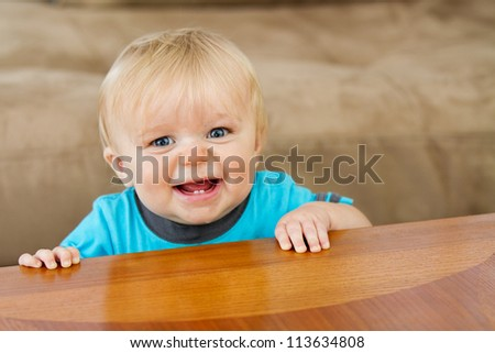 Toddler trying to hold himself up nice and proud at the edge of the table