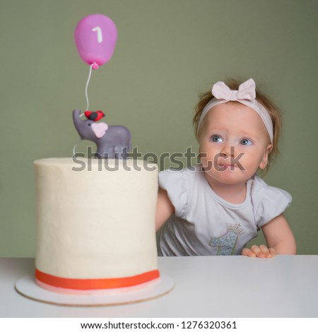 Toddler trying to touch birthday cake with her finger. Positive emotions on the face of little girl. Little girl looking at birthday cake with number one on it. Smiling toddler with pie.