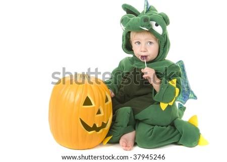 Toddler wearing halloween dragon costume with pumpkin