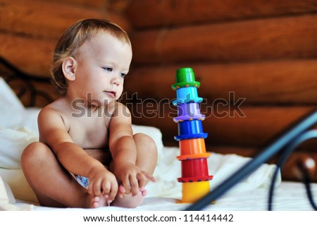 toddler with toy sitting on the bed