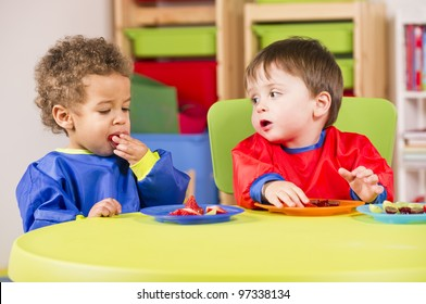 A stock photo of toddlers eating fruit and having a chat in the playroom