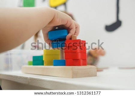 Toddlers playing multicolored educational games, mosaic and puzzles table. #1312361177
