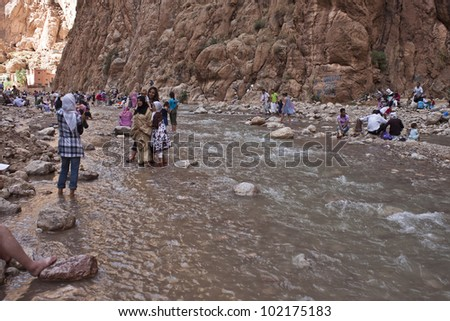 TODRA, MOROCCO - AUGUST 4: Unidentified local people bath on August 4, 2010 in Todra, Morocco.Todra Gorge is a canyon in the eastern part of the High Atlas Mountains in Morocco,near  town of Tinerhir. - stock photo