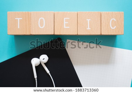 TOEIC listening; Five wooden blocks with TOEIC text of concept, a black notebook, a piece of paper, and a pair of earphones. ストックフォト ©