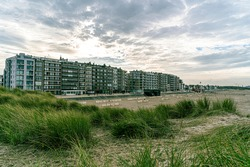 Toeristic pictures of coastcity in flanders Zeebrugge.  Appartements with view to the northsea in flanders.  Bright day combined with dunes sea grasses that lead the eye to blankenberge.