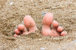 toes buried in the sand of the sea on the beach, foot on the sand, summer theme