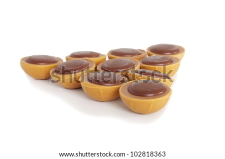 toffee chocolates arranged in a triangle on white background