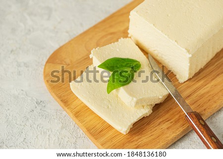 tofu, paneer, soy cheese, curd cheese, brynza, feta, Adyghe cheese with Basil and a knife on a wooden cutting Board on a light background