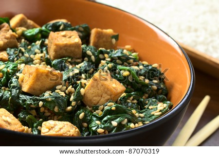 Tofu, spinach and sesame stir-fry fried with garlic and ginger, cooked rice in the back (Selective Focus, Focus on the front of the tofu one third into the bowl)