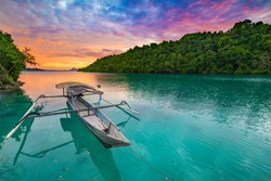 Togian Islands Indonesia sunset over caribbean sea, dramatic sky, traditional boat floating on blue green lagoon in the Togean Islands, Sulawesi, travel destination in Indonesia.