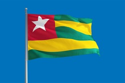 Togo national flag waving in the wind on a deep blue sky. High quality fabric. International relations concept.