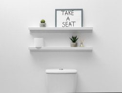 Toilet bowl, decor elements and funny sign near white wall. Bathroom interior