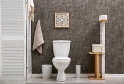 Toilet bowl near dark wall in modern bathroom interior