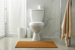 Toilet bowl near shower stall in modern bathroom interior