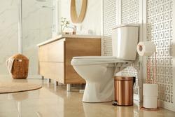Toilet bowl near wooden screen in modern bathroom interior