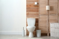 Toilet bowl near wooden wall in modern bathroom interior. Space for text