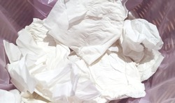 Toilet paper in dustbin, abstract background.